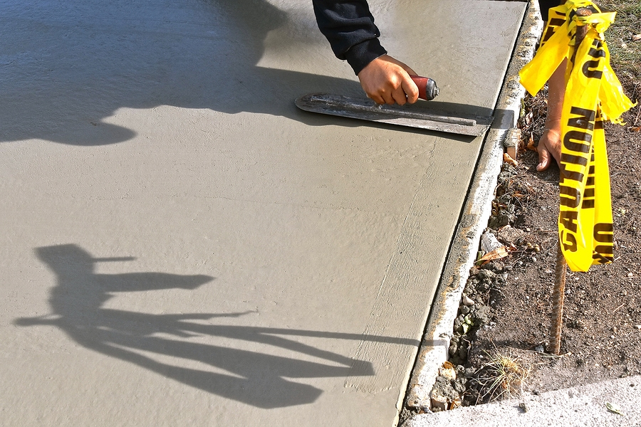 worker working on concrete driveway
